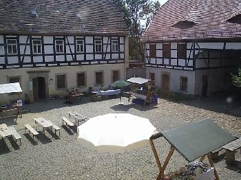Ein Blick aus dem Fenster des Büros der Auterwitzer Landschaftspflegehof GmbH eröffnet eine herrliche Perspektive auf das sanierte Fachwerk des Mattheshofs. Rechts im Bild das Torhaus und links das alte Wohnhaus.